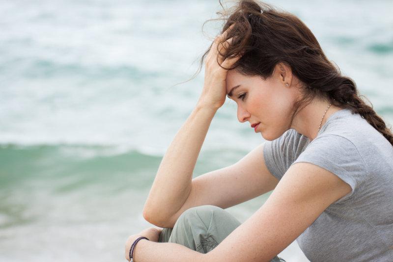 海辺で悩む女性