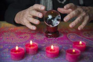水晶に手をかざす占い師